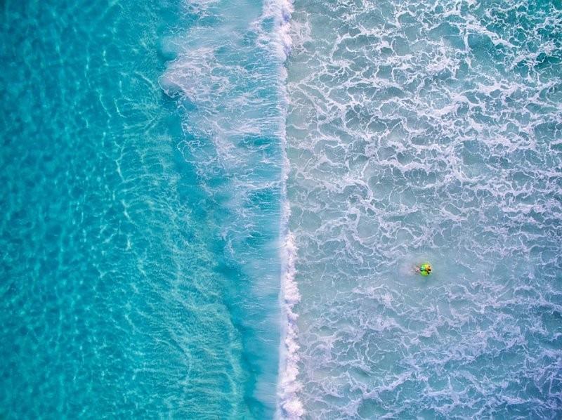 海灘水面的鳥瞰圖,浪花剛好將畫面劃分為左右兩半。(圖片來源:Kirk Hille / Skypixel.com)