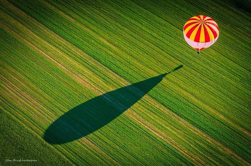 一大片留白的大草原,讓空中熱氣球的影子有長長的投射在地面上,令畫面變得更為壯觀。