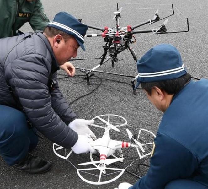 操作人員檢查被天網無人機捕捉的模擬入侵無人機(圖片來源:翻攝自《產經新聞》)。