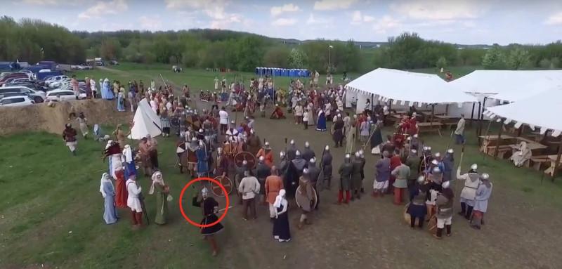 中年漢(紅圈者)突然從人群走出,向空拍機投擲長矛。