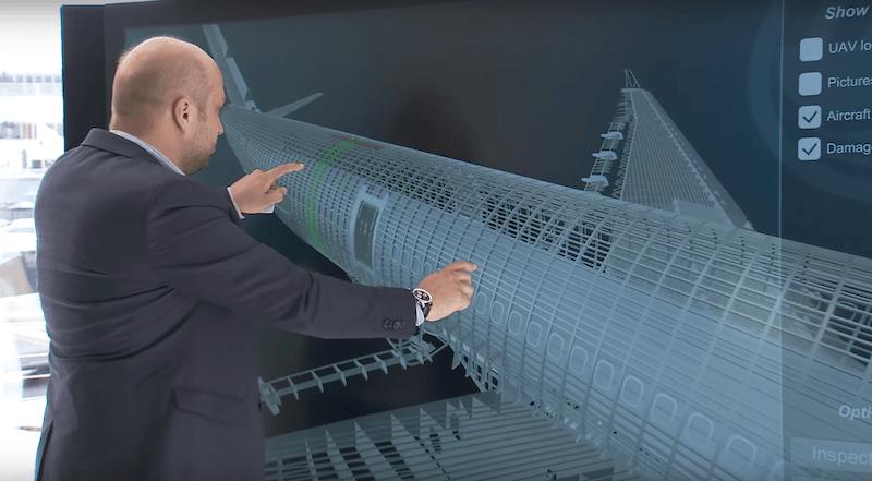 檢查人員在大型觸控屏幕上檢視飛機的 3D 模型。