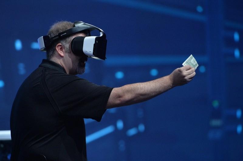 戴上 Project Alloy 眼鏡 的 Intel 工作人員示範如何在虛擬世界中展示手中的鈔票。