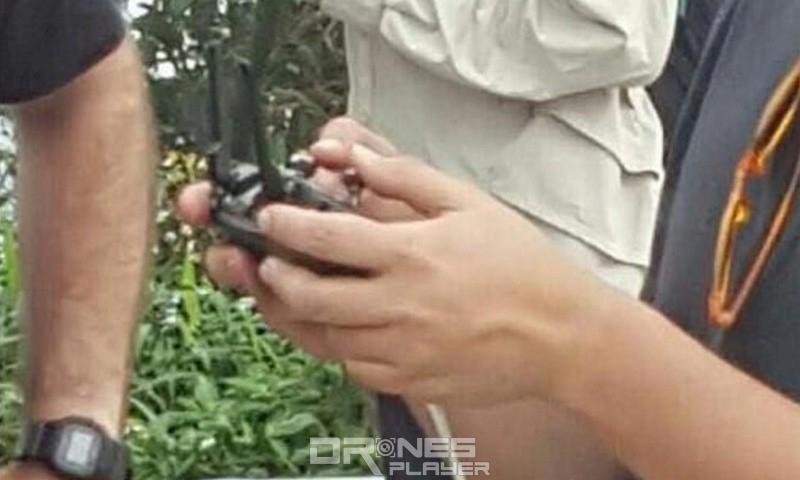 諜照中的 DJI Mavic 遙控器正被一名成年男生手持操控,看似體積不算太大。同時,請留意有一支白色線材從遙控器垂掛出來,估計是用作連接智慧型手機或平板電腦的 USB 線。
