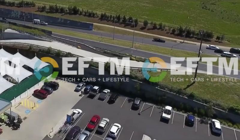 空拍機飛越停車場和馬路上空。
