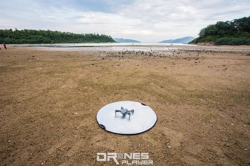 圖中示範以攝影用反光板,充當航拍機的升降保護墊。