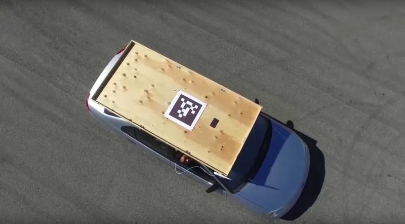 自動降落系統設計簡單,就是在汽車頂放上一塊木板、印上二維碼的紙張和發放 GPS 訊號的手機。