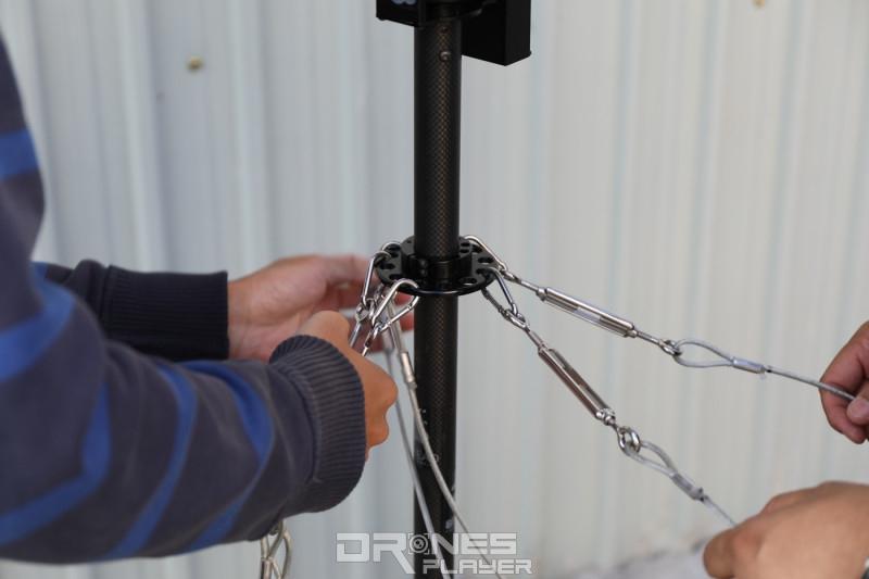 通過金屬扣和纜線緊繫著支撐相機托盤的碳纖管。